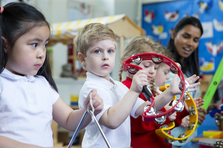 Nursery children playing with musical instruments in the classroom. One little boy is looking at the camera with a tambourine. Stock Photo