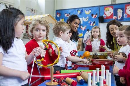 niños de la guardería que juegan con los instrumentos musicales en el aula. Una niña está mirando a la cámara con una pandereta.
