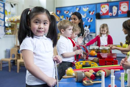 保育園教室で楽器で遊んでいる子供たち。一人の小さな女の子は、タンバリンを持つカメラを見ています。