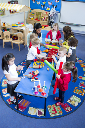 Nursery children playing with musical instruments in their music lesson with teachers. They are in the classroom.
