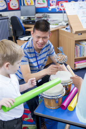chinese drum: Nursery teacher playing with musical instruments with his student. Stock Photo