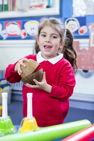 making music: Little girl in nursery making music with coconut shells in her lesson. She is looking at the camera.