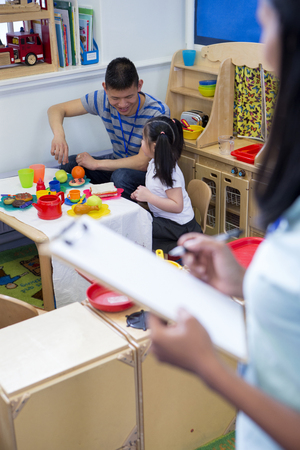 spectating: Male teacher playing in a toy kitchen with a nursery student. There is a teacher in the foreground with a clipboard who is watching them.