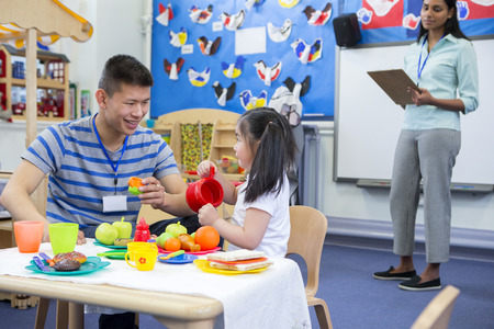 Male teacher playing in a toy kitchen with a nursery student. There is a teacher in the background with a clipboard who is watching them.