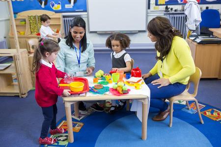 교실에서 자신의 보육 학생들과 플라스틱 주방 장난감을 가지고 노는 교사.