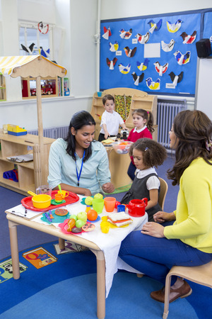 Teachers playing with plastic kitchen toys with their nursery students in the classroom.