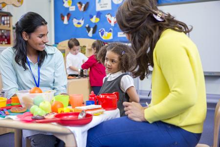 Leerkrachten spelen met plastic speelgoed keuken met hun kwekerij leerlingen in de klas.