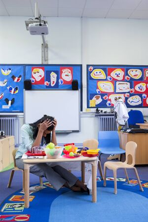 head toy: Stressed nursery teacher in a classroom. She has her head in her hands and is sitting at the toy table. Stock Photo