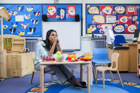 maestra d'asilo sottolineato in una classe. Lei è seduta al tavolo giocattolo.