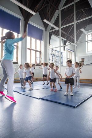 educacion fisica: lección de educación física con los estudiantes de enfermería. Se hace la estrella salta con su profesor.