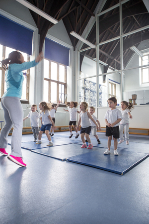 physical education: Physical education lesson with nursery students. They are doing star jumps with their teacher. Stock Photo