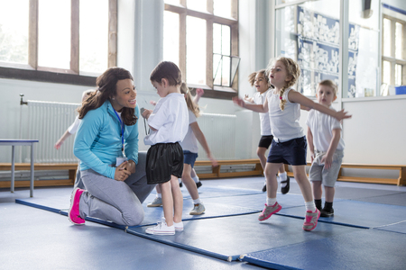 children sport: Nursery teacher reassuring one of her students during a physical education class. Stock Photo