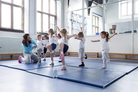 physical education: Nursery teacher helping one of her students during a physical education lesson. Stock Photo