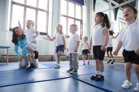 children sport: Nursery teacher helping one of her students during a physical education lesson. Stock Photo