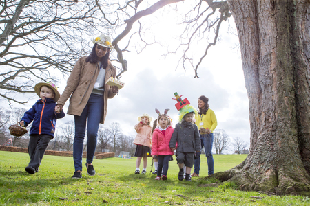 Elevated view of teachers doing activities with children in nursery teachers and students doing an easter egg hunt outdoors they are wearing handmade hats negle Images