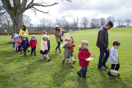 egg hunt: Nursery teachers and students doing an Easter egg hunt outdoors. They are wearing handmade hats and carrying baskets.