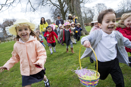 Nursery children running across a field during their outdoor Easter egg hunt, they are wearing handmade hats and carrying baskets.