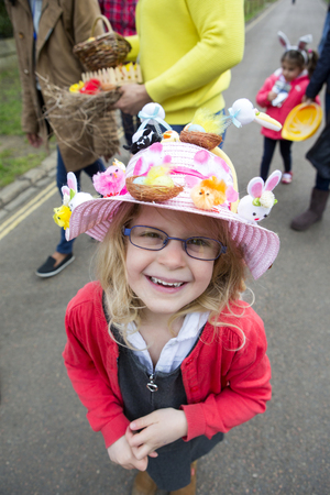 Little girl looking up and smiling at the camera with an Easter hat on during her nursery Easter egg hunt.