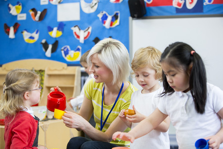 Nursery teacher playing kitchen roleplay with her students in the classroom. she is pouring a pretend cup of tea for a little girl.