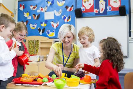 Nauczyciel przedszkola grając kuchnia roleplay z jej uczniów w klasie. Zdjęcie Seryjne