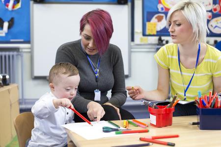 Kleuteronderwijzer zitten met een ouder en haar zoon het syndroom van Down in de klas. ze hebben het over de kleine jongens vooruitgang. Stockfoto