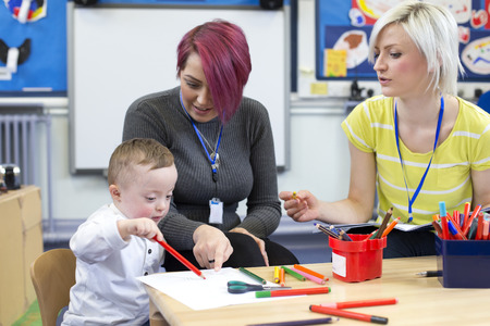 maestra preescolar: profesor de cuarto de niños sentados con un padre y su hijo de Síndrome de Down en el aula. que están discutiendo el progreso niños pequeños.