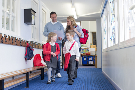 Parents and students walking down a primary school corridor. the parents are looking at some paperwork and the children are talking. Stockfoto