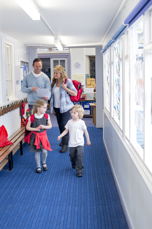 Parents and students walking down a primary school corridor. the parents are looking at some paperwork and the children are talking. Standard-Bild
