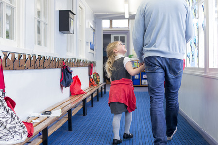 waist down: Little girl walking through her nursery corridor with her father. She is holding his hand and looking up to him with a smile on her face.