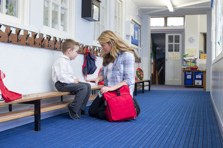Young mother scolding her son in the corridor for bad behaviour in nursery.