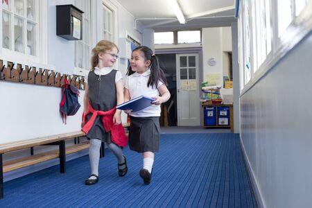 Due studenti vivaio femminile camminare insieme lungo il corridoio. Uno è in possesso di un libro e sono entrambi ridere in conversazione.