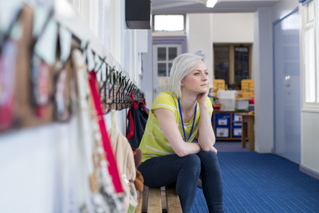 Young, female teacher sitting on a bench in the cloakroom of school. She is looking pensively out of the window. Stock Photo