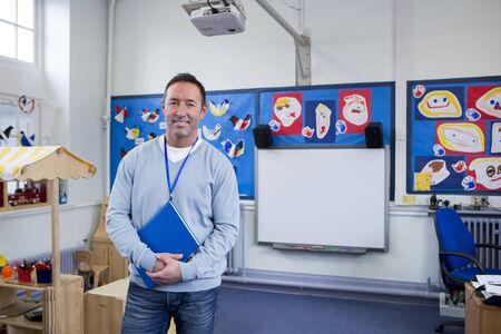 Männliche Kindergartenlehrer in einem Klassenzimmer. Er steht und lächelt für die Kamera mit einem Buch in der Hand.