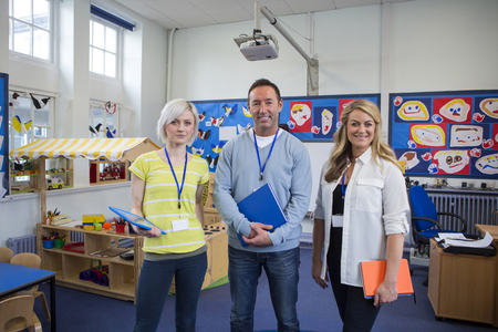 Three teachers standing in the classroom of a school building. They are holding school work and smiling at the camera. Stockfoto