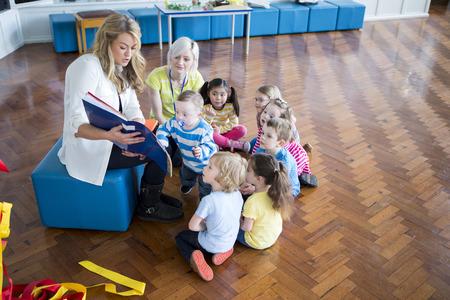 Malá skupina mateřských studentů sedí kolem učitele v jejich školní chodbě. Ona čte knihu k nim.