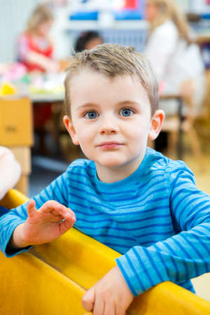 sand pit: Portrait of a little boy who is playing in a sand pit at nursery. He is looking at the camera.
