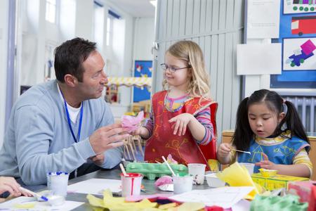 verlobt: Männliche Lehrer zu einem seiner Kindergarten Schüler im Klassenzimmer zu sprechen. Sie machen Kunst und Handwerk. Lizenzfreie Bilder