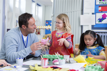 elementary school: Male teacher talking to one of his nursery students in the classroom. They are doing arts and crafts. Stock Photo