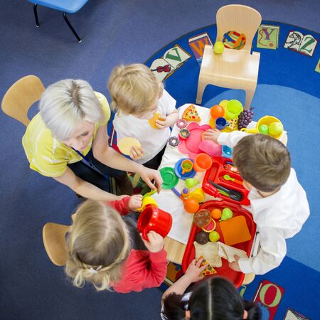 Overhead view of nursery students roleplaying a restaurant with their teacher in the classroom.