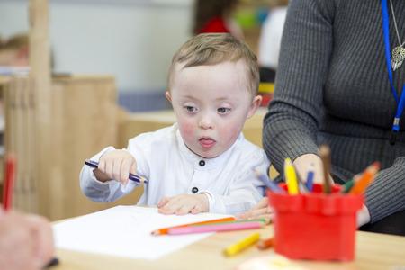 그의 보육에서 착 색 하 고 다운 증후군 아이. 그의 교사는 그 옆에 앉아있다.