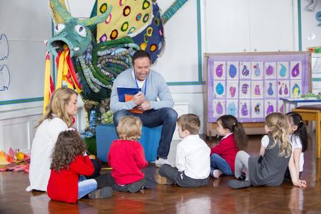 niños sentados: Pequeño grupo de niños de la guardería están sentados en el suelo en el pasillo de la escuela en torno a su maestro. Él es la celebración de los libros y hablar con ellos. Foto de archivo