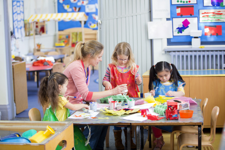 females only: Teacher and nursery students doing arts and crafts in the classroom.