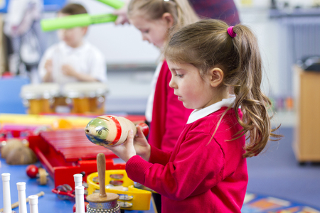 percussion: Little girl in nursery playing with a guiro. She is in the classroom with other children.