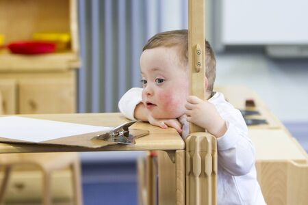 peers: Little boy with Down Syndrome at nursery. He is resting his chin on the bench, spectating his peers who are out of the frame.