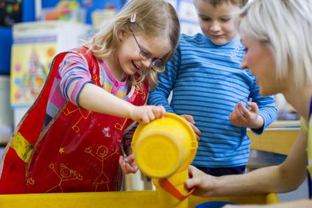 educadores: profesor de cuarto de niños jugando en el agua de mesa con dos hijos.
