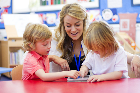 engaging: Female nursery teacher using a digital tablet with two students in the classroom.