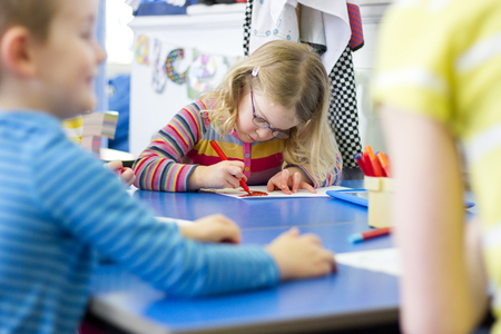 Little girl sitting at a table in her nursery classroom. She is colouring in with felt tip pens. Stock Photo