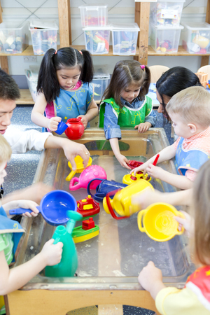 Group of nursery children playing at a water table with their teacher.