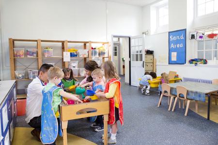 教室で保育園の子供たちのグループです。ほとんど水のテーブルでプレーしているし、3 人の子供が砂のテーブルで遊んでいます。
