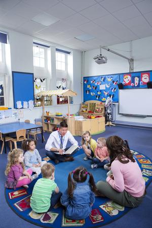 교실에서 바닥에 앉아 보육 어린이의 그룹입니다. 남성 교사는 책을 읽고 있습니다.